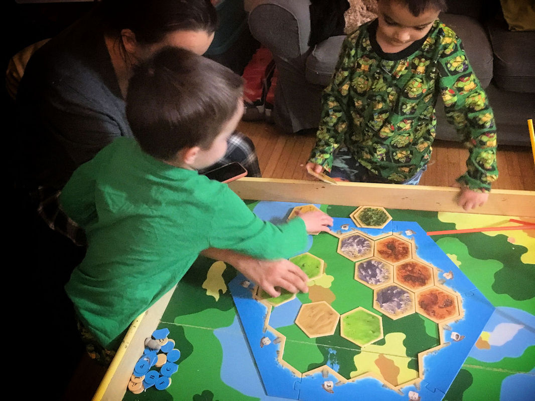Twin boys playing their first match of Settlers of Catan like Monopoly. A great example of kids making up their own board game rules!